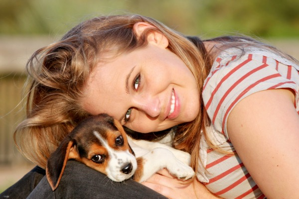 happy young woman with her pet beagle puppy dog outside